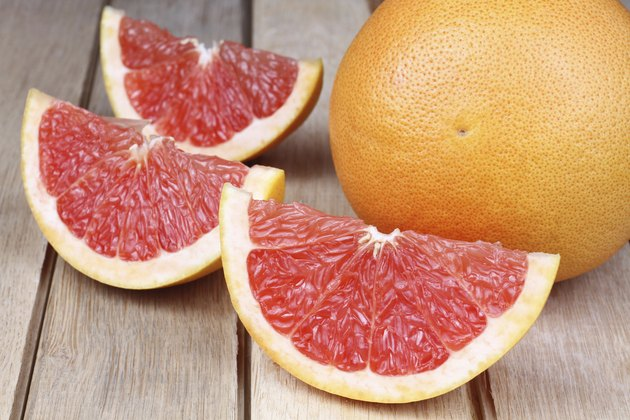Sliced red grapefruit on a wooden background