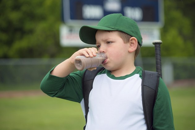 Child baseball player drinking chocolate milk