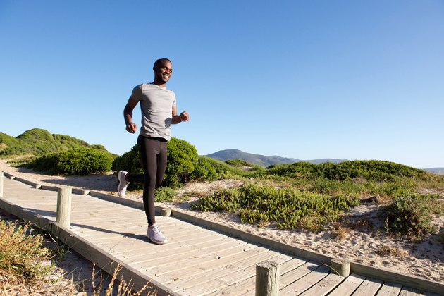 Healthy young african man running on path at the beach