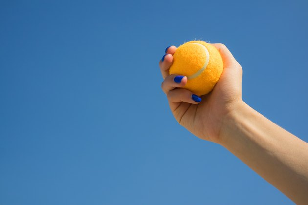 Female hand holds a bright orange tennis ball