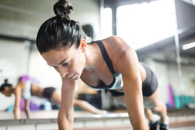 Young fit female doing push-ups in gym