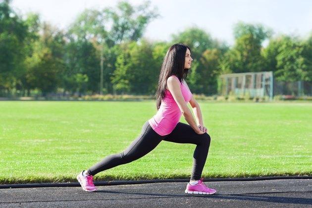 woman sport on stadium leg stretching exercises