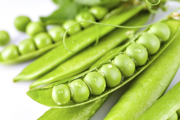 Pods of green peas with drops on white background