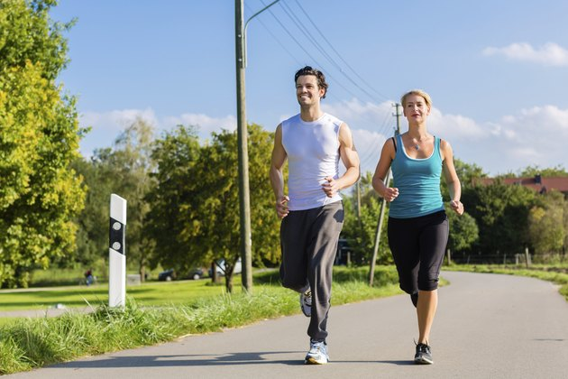 Sport couple running and jogging on rural street