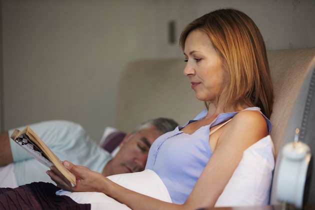 Middle Aged Couple In Bed Together With Woman Reading Book