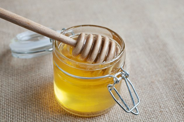 Honey jar isolated on jute background