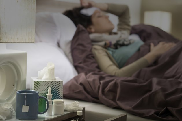 Tissue, flu medicines ill woman bedside table
