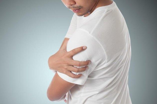 man having shoulder pain on blue background