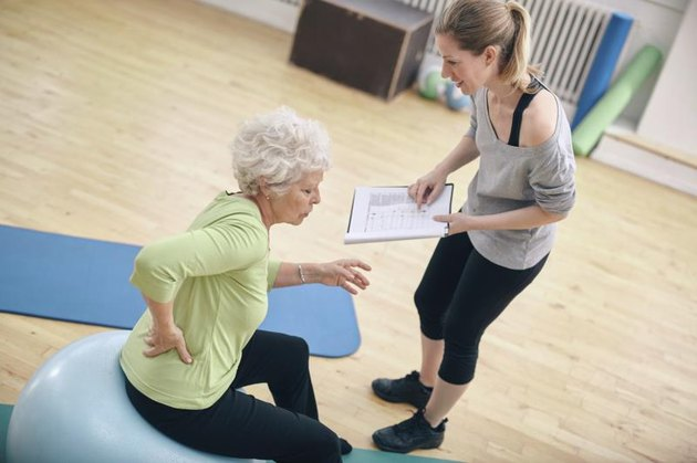 Senior woman sitting on a fitness ball with her female instructor explaining exercise plan at gym. Physical therapist with old woman at rehab.