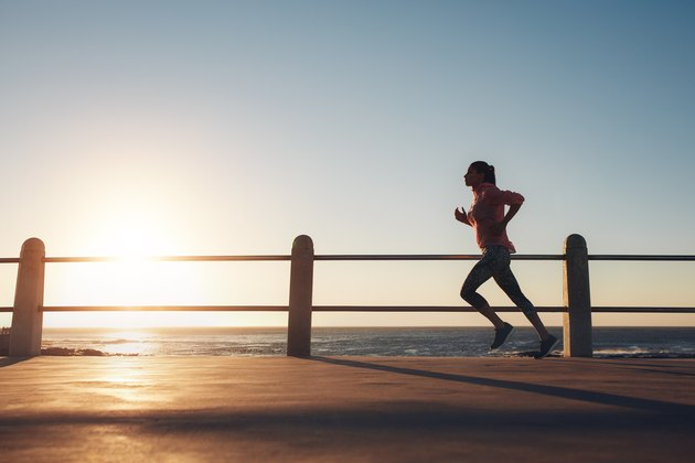 Image of fit sportswoman jogging on a road by the sea during evening. Female runner training at sunset.