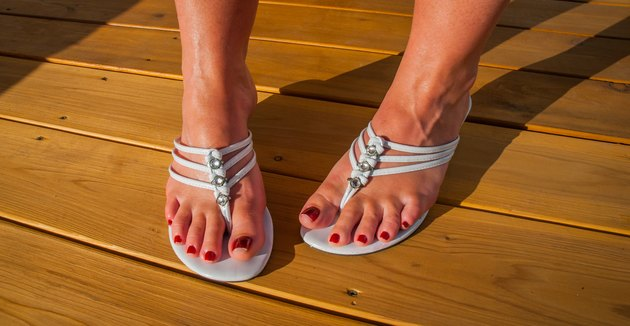 Womans feet in white tri strap summertime sandals.