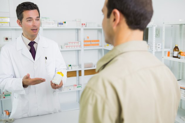 Pharmacist holding and pointing at a box of pills in front of a man