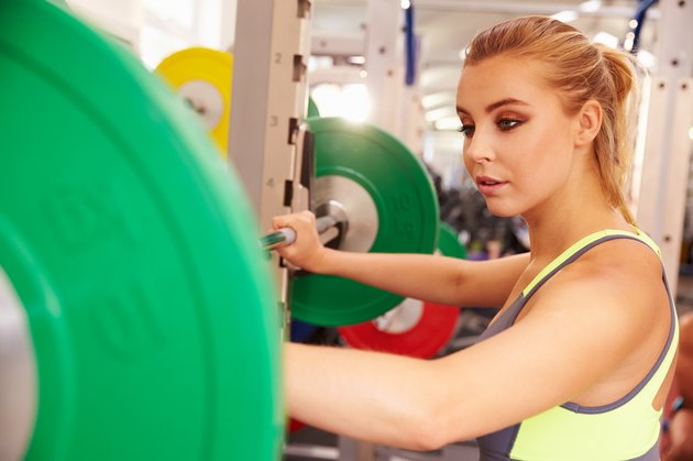 Woman preparing to lift barbells at in a gym