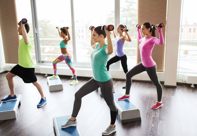 group of people with dumbbells and steppers