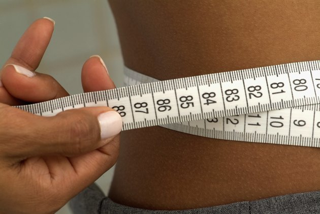 Close-up of a woman measuring his waist with a measuring tape