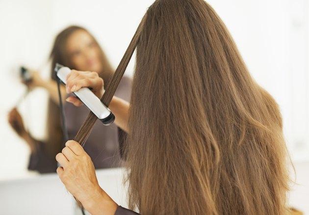 woman straightening hair with straightener . rear view