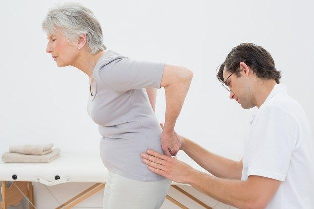 Physiotherapist examining senior woman's back