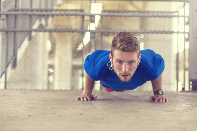 Young man doing push ups, warming up for running.