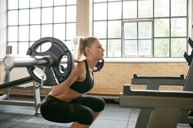 Female working out in a gym doing squats