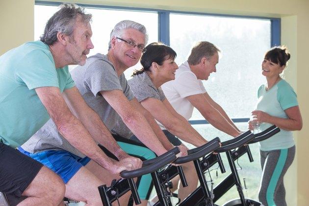 Group of seniors using spinning bikes