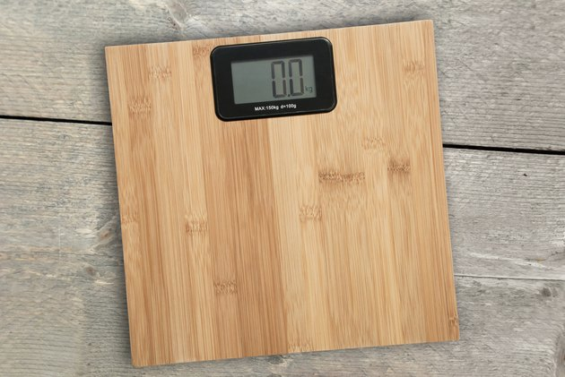 Electronic floor scale on a wooden background