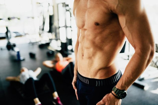 Attractive male torso in gym flexing abs