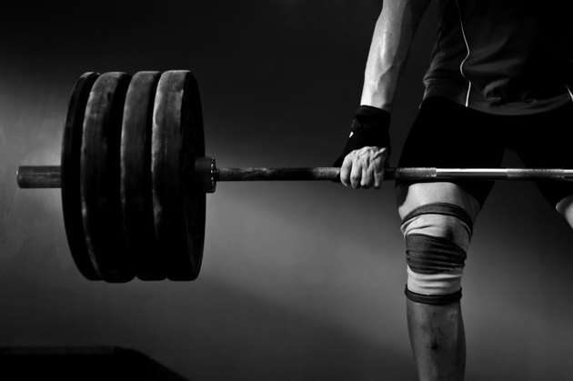 a photo of a man lifting barbell and disks