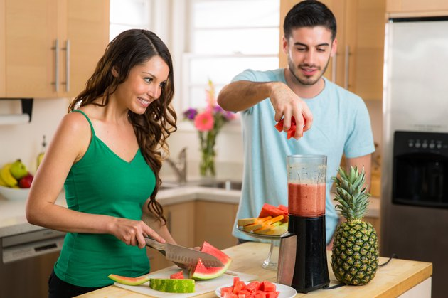 Couple lovers man woman make a smoothie fresh fruits blender