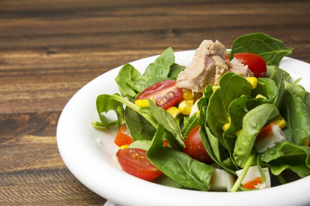 Fresh spinach salad with tuna and corn, cherry tomatoes