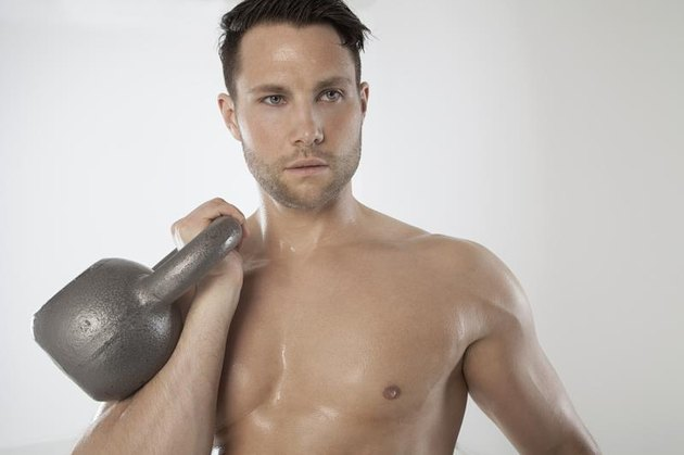 male athlete holding a kettlebell in one hand to his chest