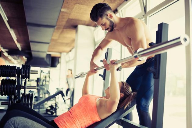 A personal trainer assists a woman with her bench press at the gym.