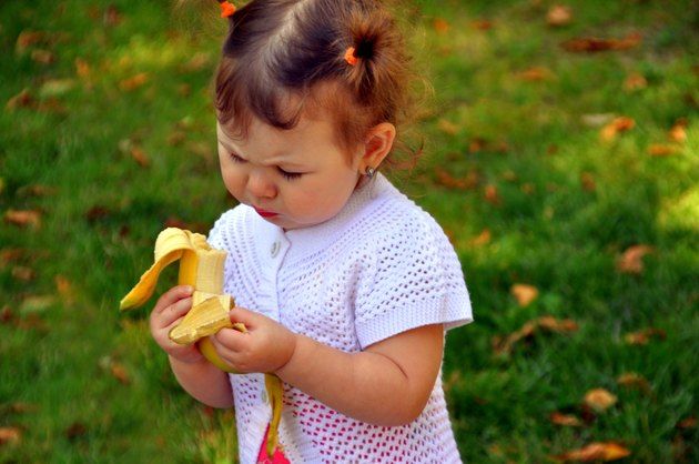 little girl eating a banana in summer outdoors