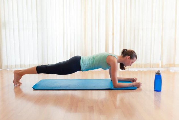 Young woman doing plank in the studio.