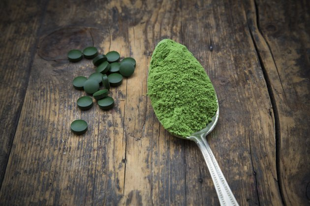 Spoon of wheatgrass powder and wheatgrass tablets