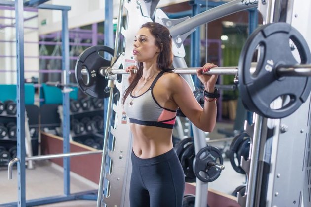 Fit woman doing shoulder press exercise with a weight bar Smith machine at gym