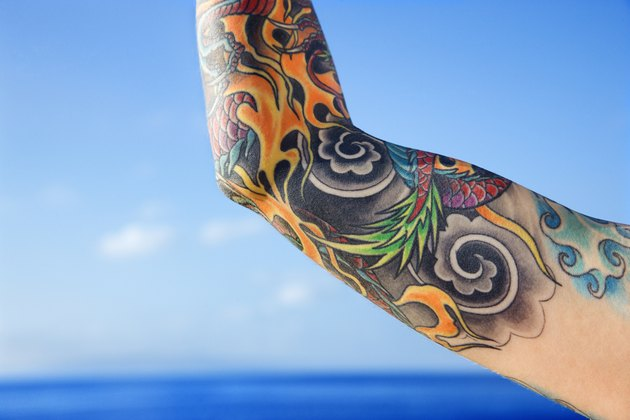 Close up of tattooed woman' || chr(39) || 's arm with Pacific Ocean in background in Maui, Hawaii, USA.
