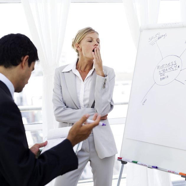 portrait of a young businesswoman yawning at a presentation
