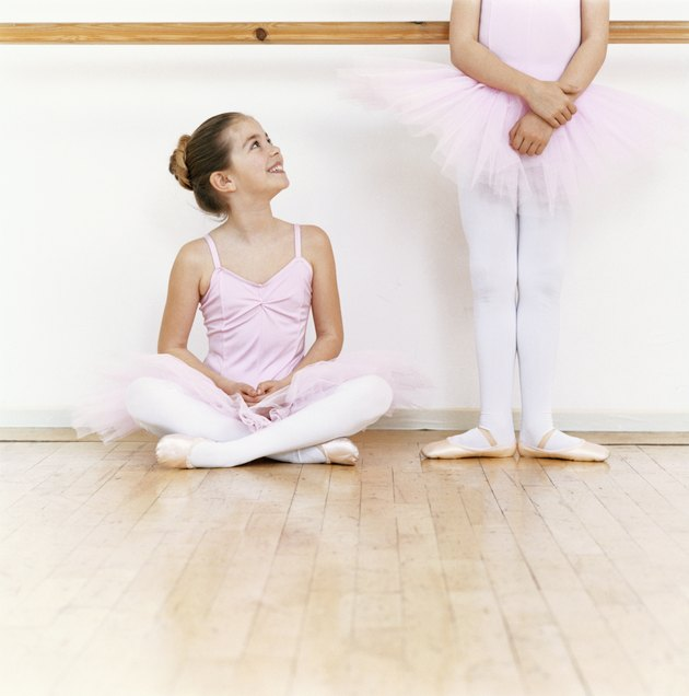 Seated Young Ballet Dancer Looking Up at Another Ballet Dancer Standing in a Dance Studio