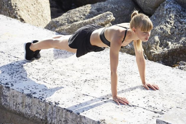 Pretty young athlete doing press ups on rocks