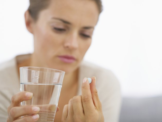 closeup on young housewife eating pills