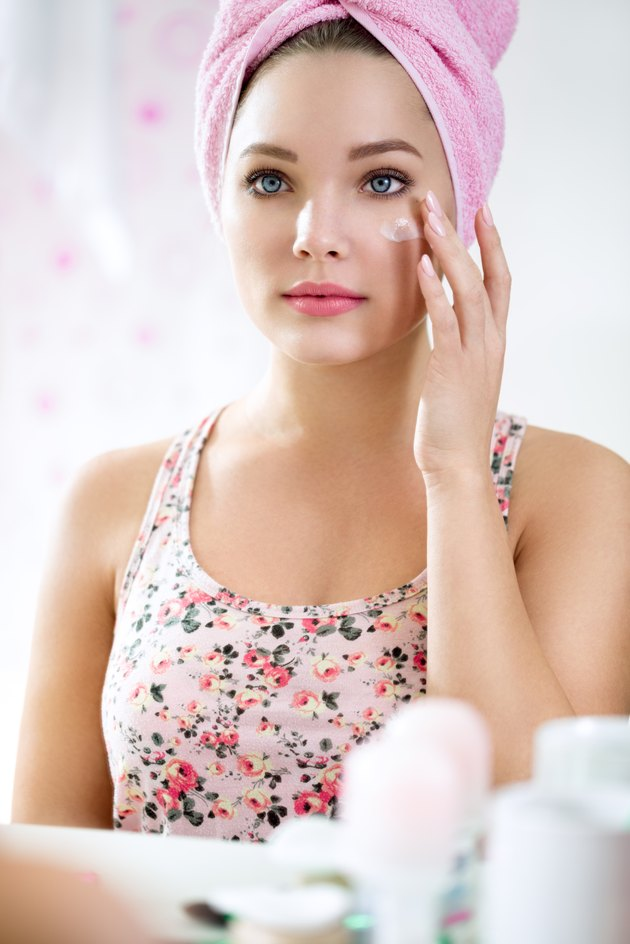Young girl in bathroom front of mirror putting cream