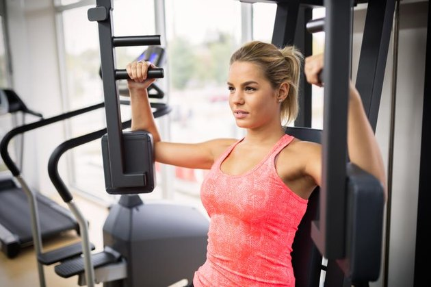 A woman does machine chest presses at the gym.