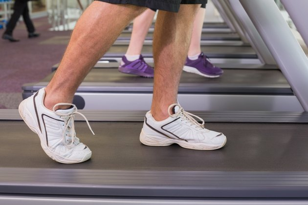 Man and woman walking on treadmills