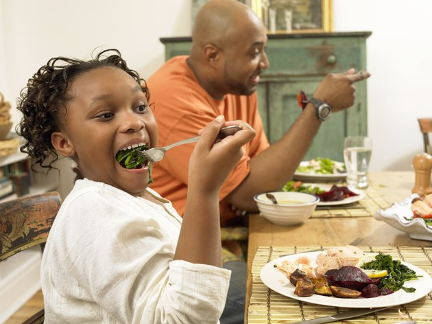 Young Girl Sits at a Table With Her Father, Eating Vegetables on a Fork