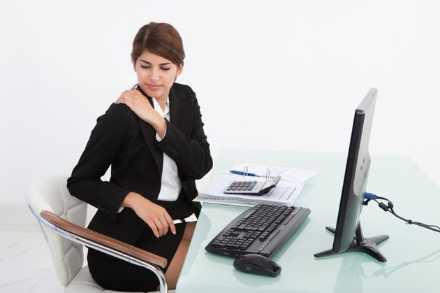 Young businesswoman having shoulder pain while working at computer desk in office