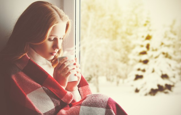 Pensive sad girl with a warming drink looking ou window
