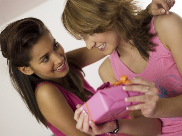 Two Girl (16-17) holding gift, smiling, close-up