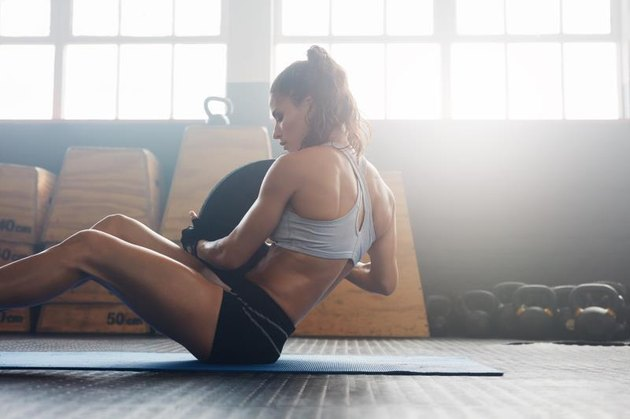 Woman doing sit ups with holding a weight plate. Fitness woman working out on core muscles at gym gym.