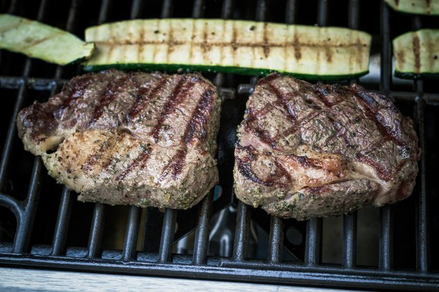 Two rib eye steak with zucchini on grill