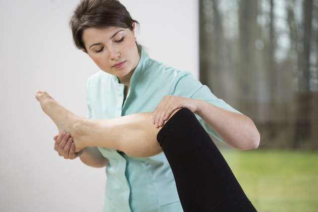 Physiotherapist flexing knee